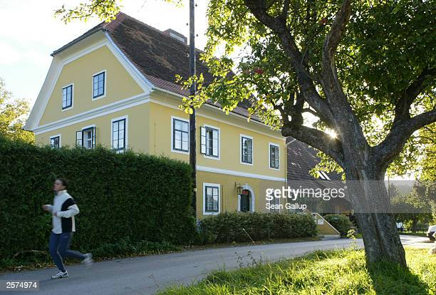 A young woman jogs past the childhood home of newlyelected California Governor Arnold Schwarzenegger October 9 2003 in the village of Thal Austria...