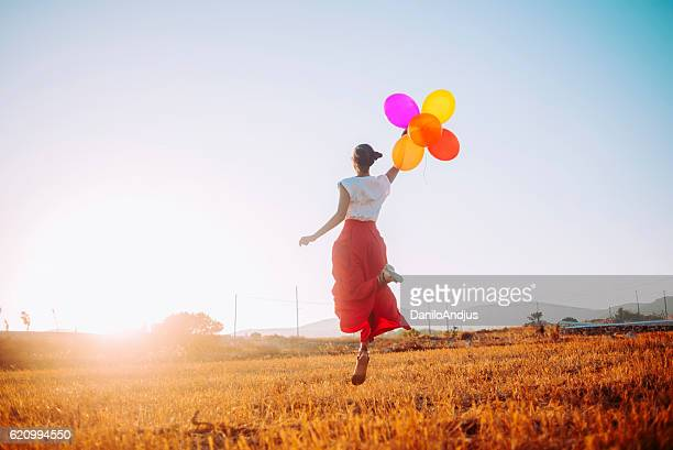 young woman joyfully jumping in the field holding colorful balloons