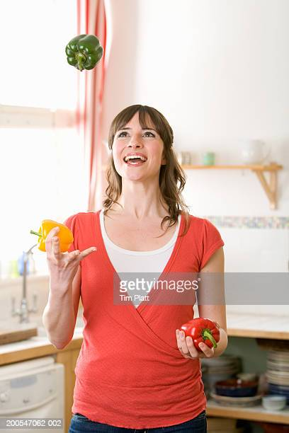 Young woman juggling green, yellow and red peppers in kitchen