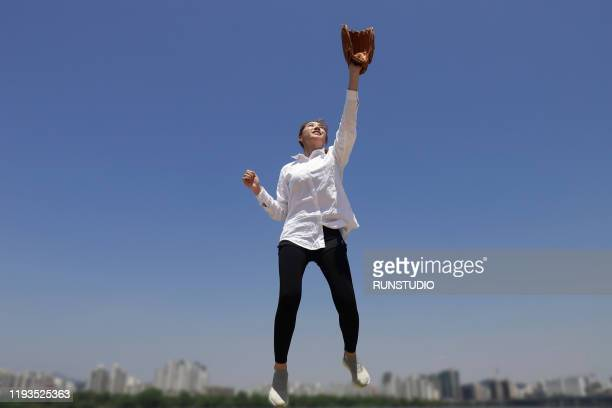 young woman jumping and catching outdoors - 投手 ストックフォトと画像