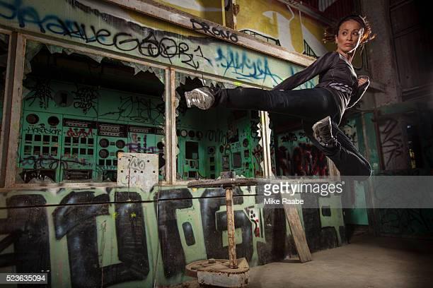 Young woman jumping and doing karate kick