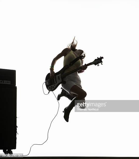 Young woman jumping and playing bass guitar, head back