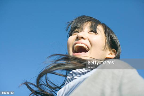 Young woman jumping and shouting, looking away