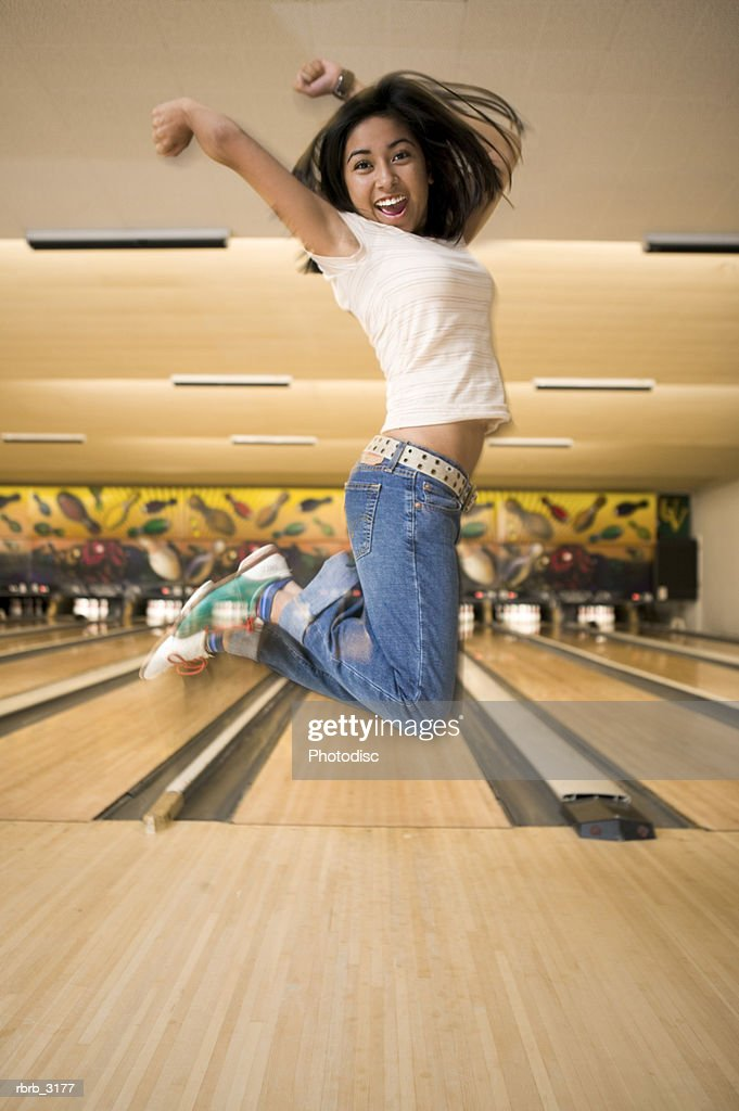 Young woman jumping at a bowling alley : Foto de stock