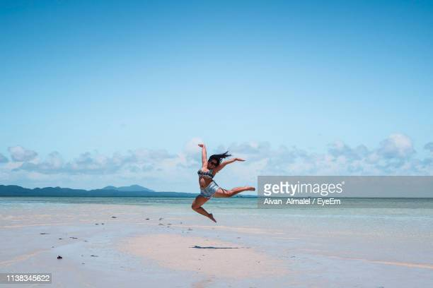 young woman jumping at beach against blue sky - filipino woman stock pictures, royalty-free photos & images