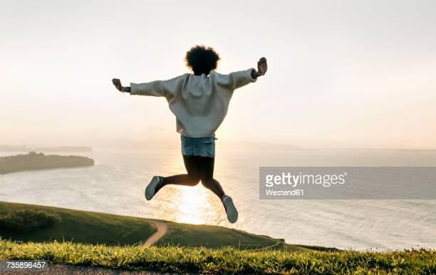 Young woman jumping at the coast at sunset