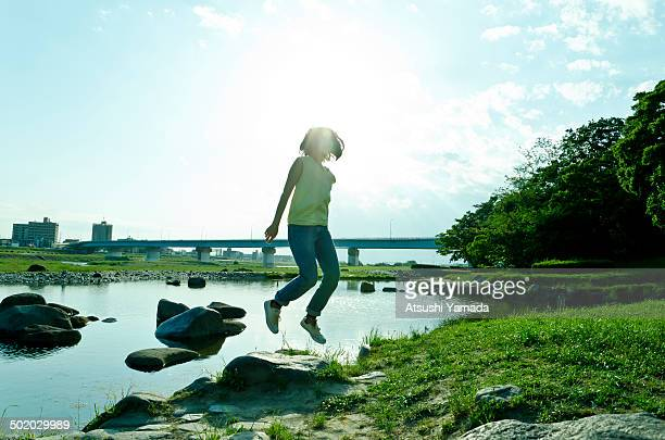 Young woman jumping beside river