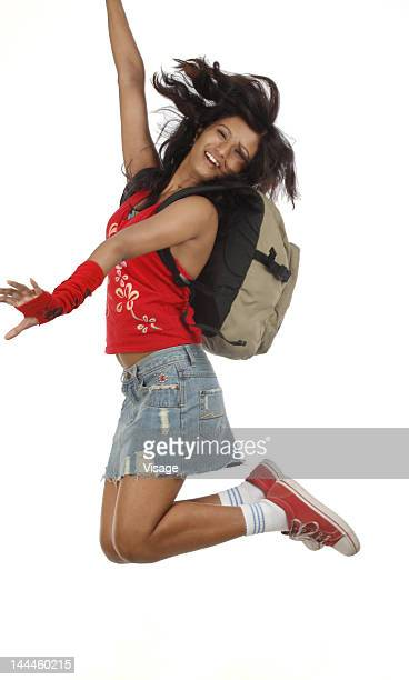 Young woman jumping carrying bag