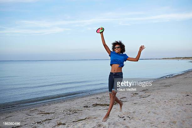 young woman jumping, catching ball on beach - nylon fastening tape stock photos and pictures
