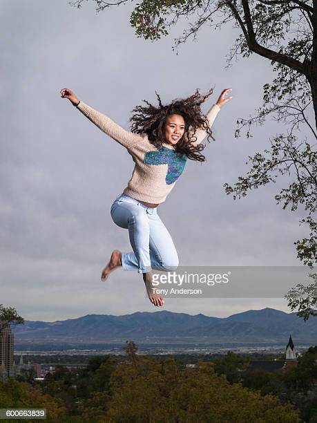 Young woman jumping city & mountains in backgrou