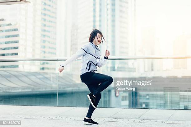Young woman jumping, exercising and warming up on city streets before run