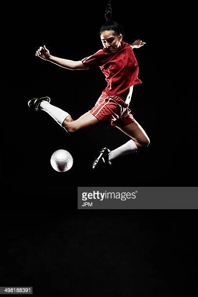Young woman jumping for football