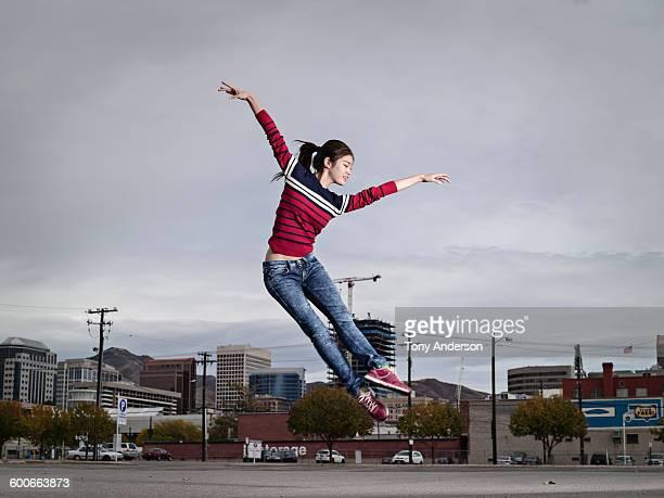 young woman jumping for joy city in background - landfahrzeug stock-fotos und bilder