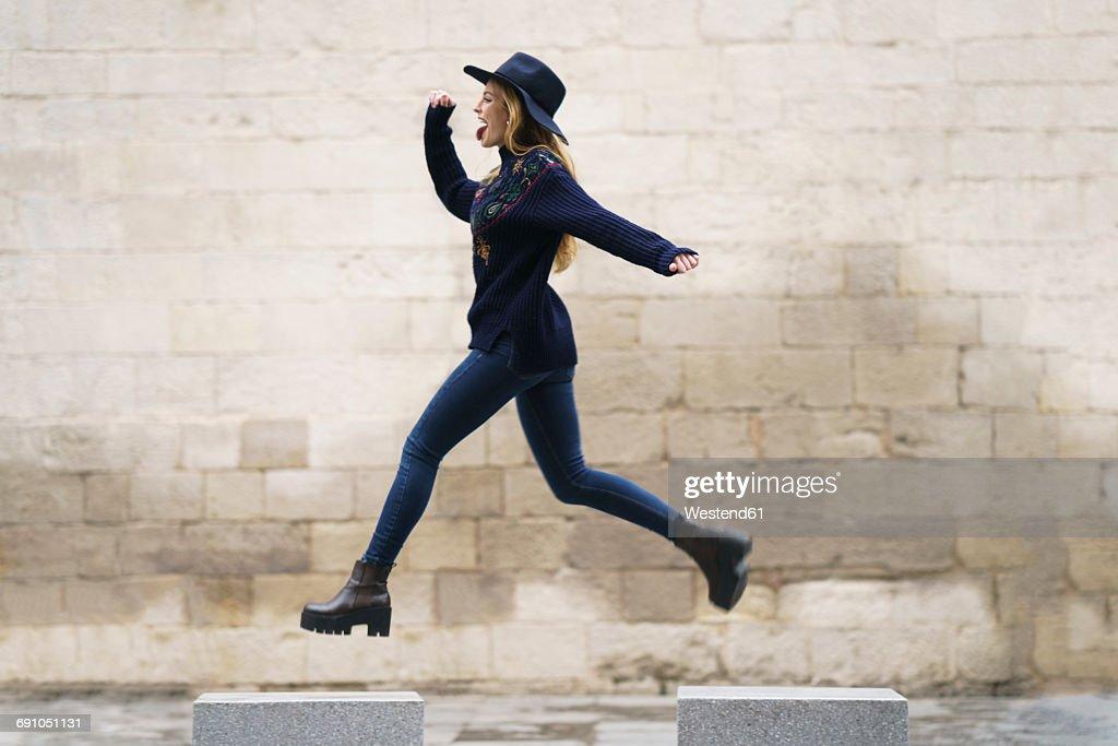 Young woman jumping from bollard to bollard : Stock Photo