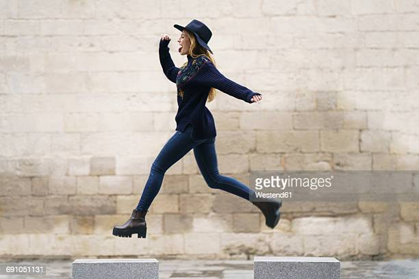 Young woman jumping from bollard to bollard