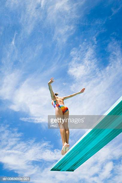 Young woman jumping from diving board, low angle and rear view