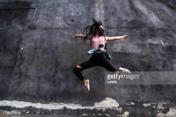 若い女性が壁の前面をジャンプ - street style ストックフォトと画像