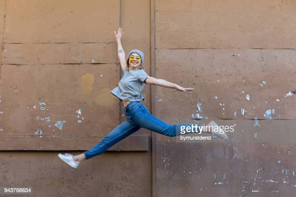 young woman jumping front of wall - libertà foto e immagini stock