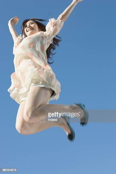 young woman jumping high - ジャンプする ストックフォトと画像