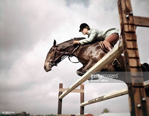 Young woman jumping horse over fence
