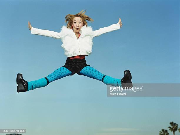 若い女性をジャンピング空気、両腕や両脚 outreached 、ポートレート