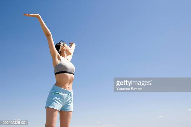 young woman jumping in air, arms outstretched, low angle view - ブラトップ ストックフォトと画像