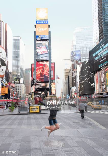 Young woman jumping in air in Times Square