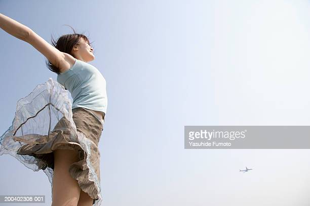 young woman jumping in air outdoors, arms outstretched - skirt blowing stock photos and pictures