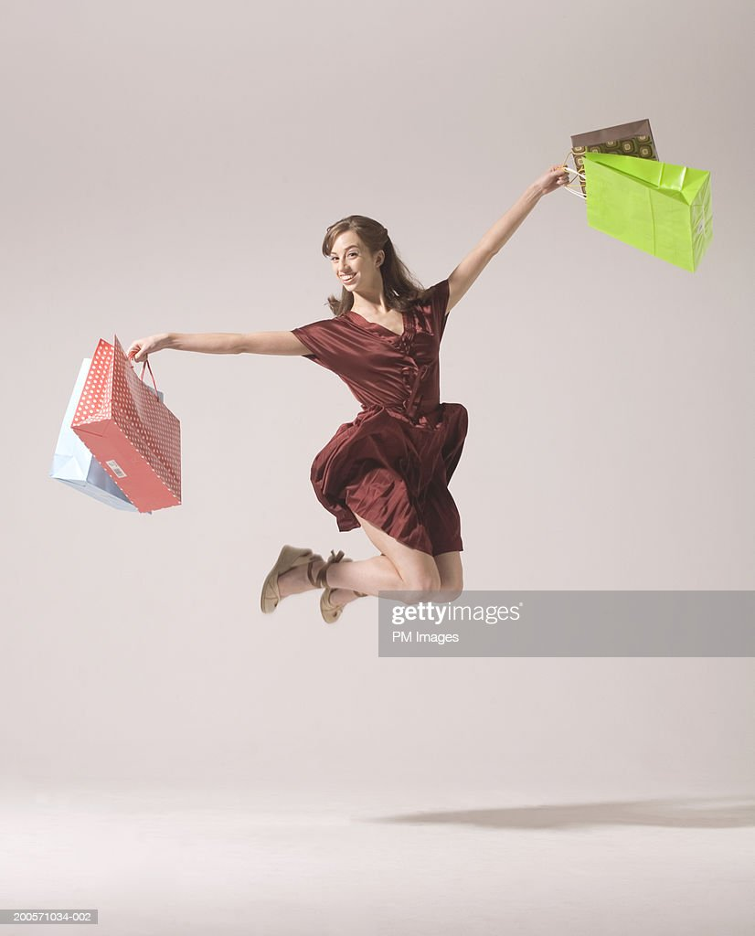 Young woman jumping in air with shopping bags, smiling : Stock-Foto