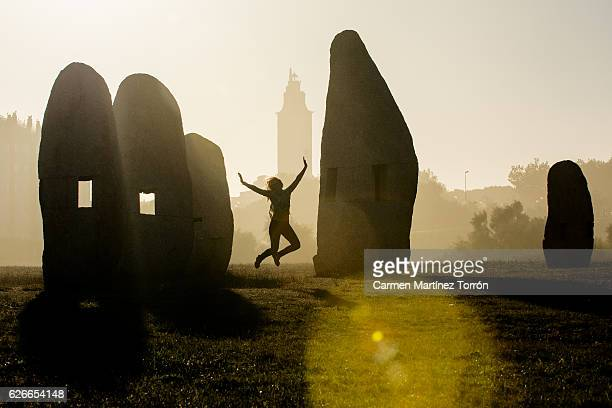 Young woman jumping in midair outdoors, in front of Hercules Tower, A Coruna, Spain.