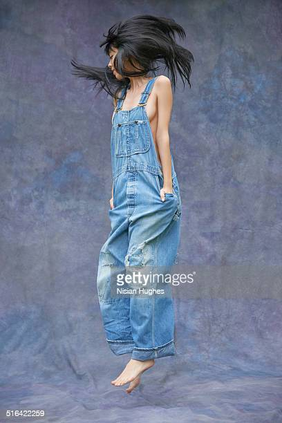 Young woman jumping in overalls