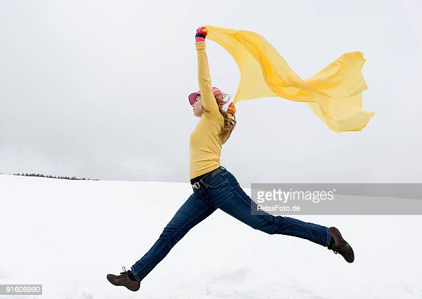 Young woman jumping in snow holding yellow scarf to wind