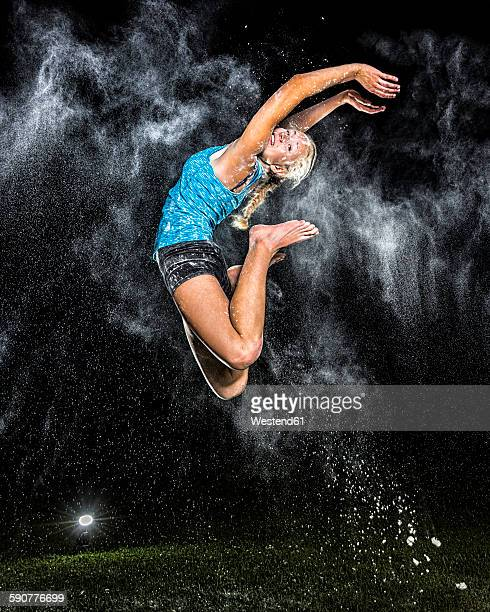 Young woman jumping in the air in between cloud of flour