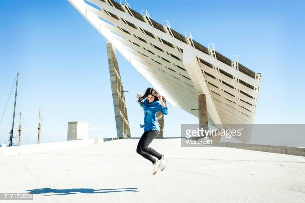 Young woman jumping in the air with solar panels in background