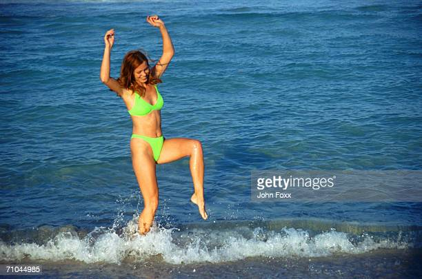 Young woman jumping in water on beach