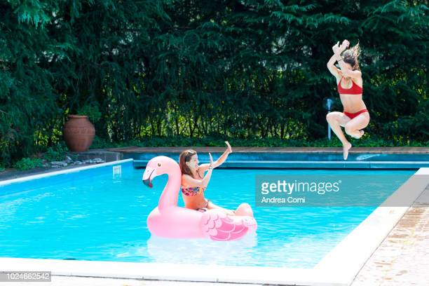 Young woman jumping into a swimming pool with a friend on a flamingo float