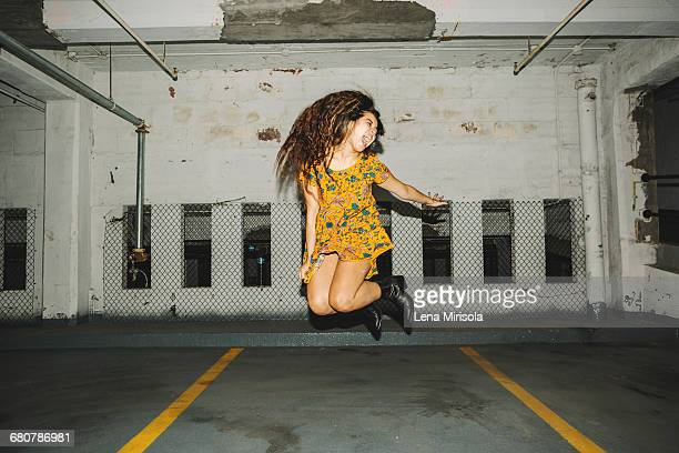 young woman jumping mid air in indoor parking lot - yellow dress stock pictures, royalty-free photos & images