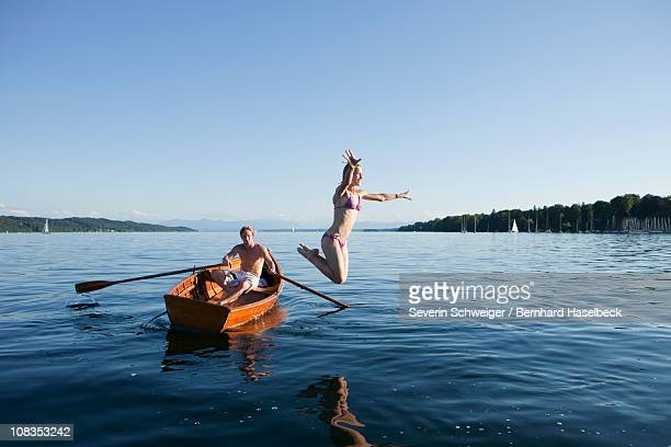 Young woman jumping off a row boat