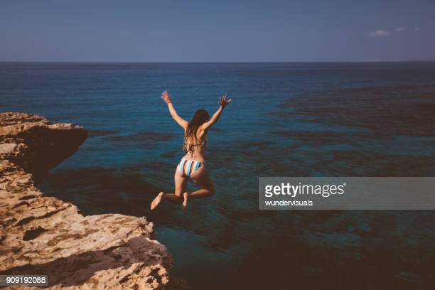 Young woman jumping off cliff and diving into blue sea