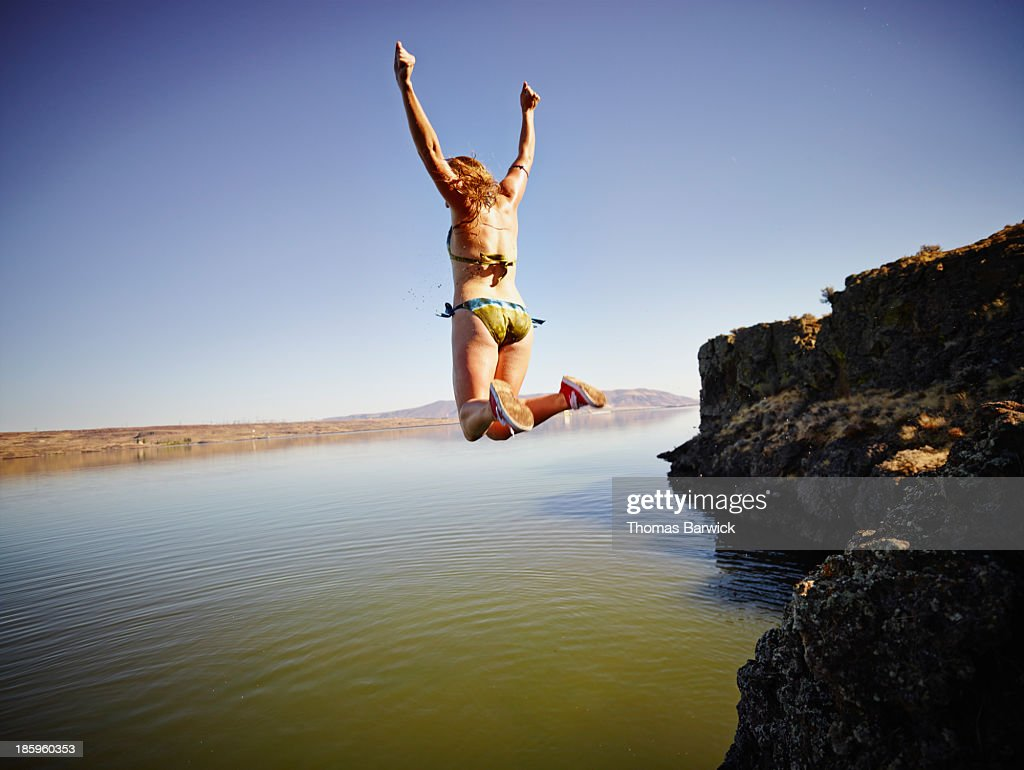 Young woman jumping off edge of cliff into river : Stock Photo