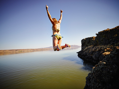 Young woman jumping off edge of cliff into river - gettyimageskorea