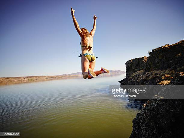 Young woman jumping off edge of cliff into river