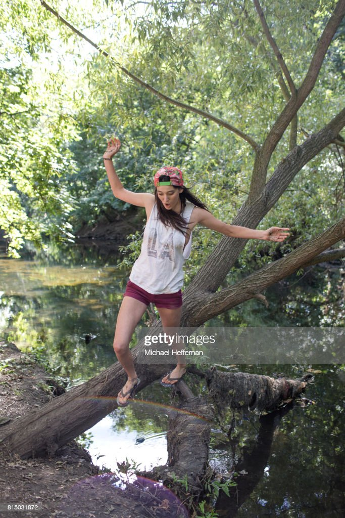 Young woman jumping off tree over river : Stock Photo