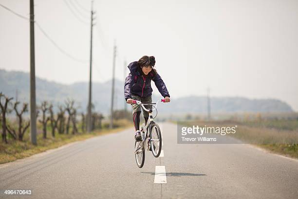 A young woman jumping on a BMX bike
