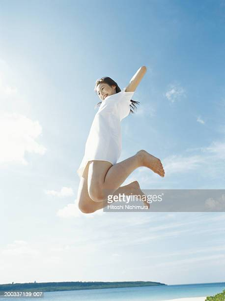 Young woman  jumping on beach, low angle view