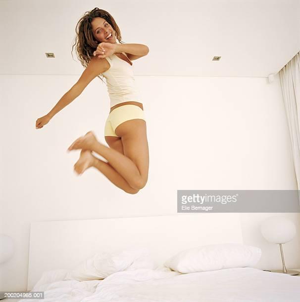 young woman jumping on bed, smiling, portrait - bragas fotografías e imágenes de stock