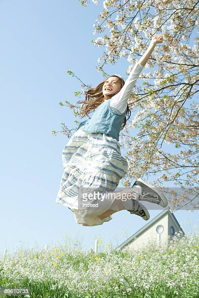 Young woman jumping on flower garden