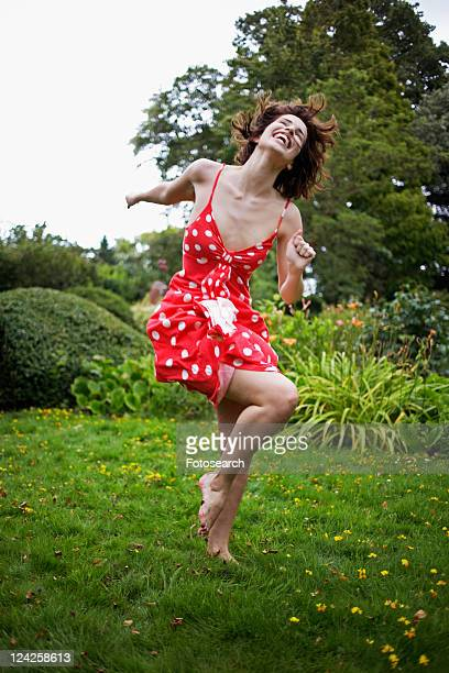 Young Woman Jumping on Grass