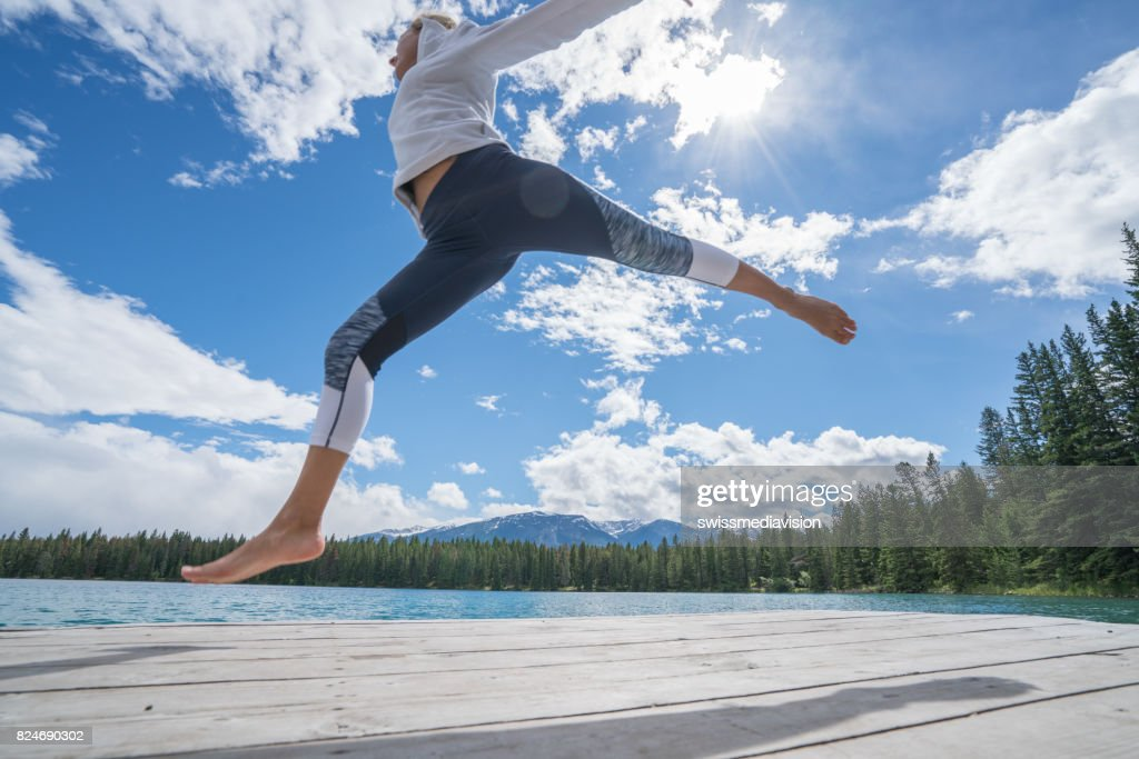 Young woman jumping on lake pier : Stock Photo