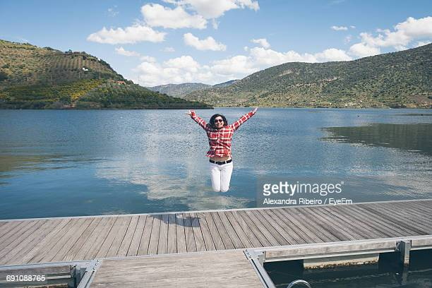 Young Woman Jumping On Pier Over Lake Against Sky